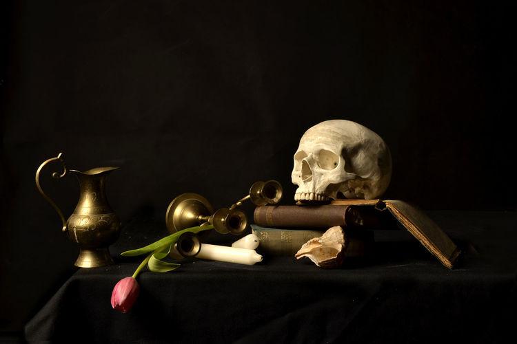 Vanitas still life. Black Background Black Color Book Books Candle Dark Death Gold Colored No People Skeleton Skull Studio Shot Tulip Vanitas Wisdom