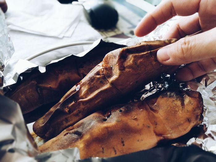 Cropped image of hand holding roasted sweet potato