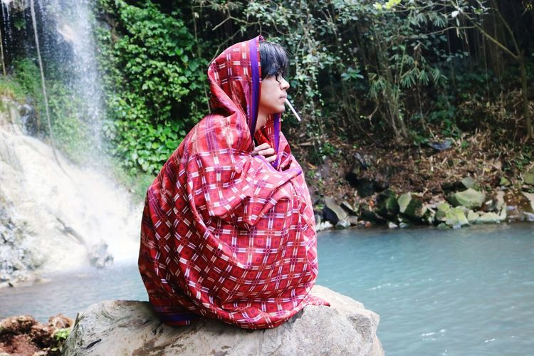 Young man wrapping in blanket sitting on rock by river