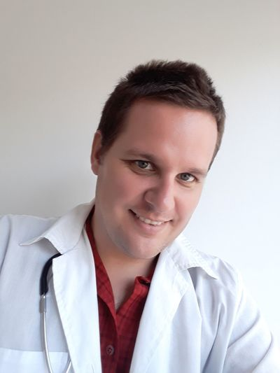 Portrait Of Male Doctor Standing Against Wall At Home