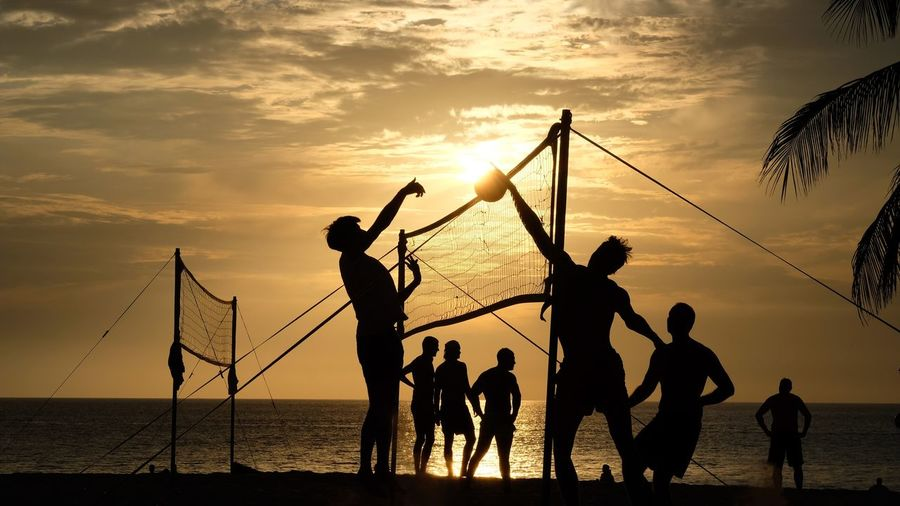 Silhouette people playing volleyball at beach against cloudy sky during sunset