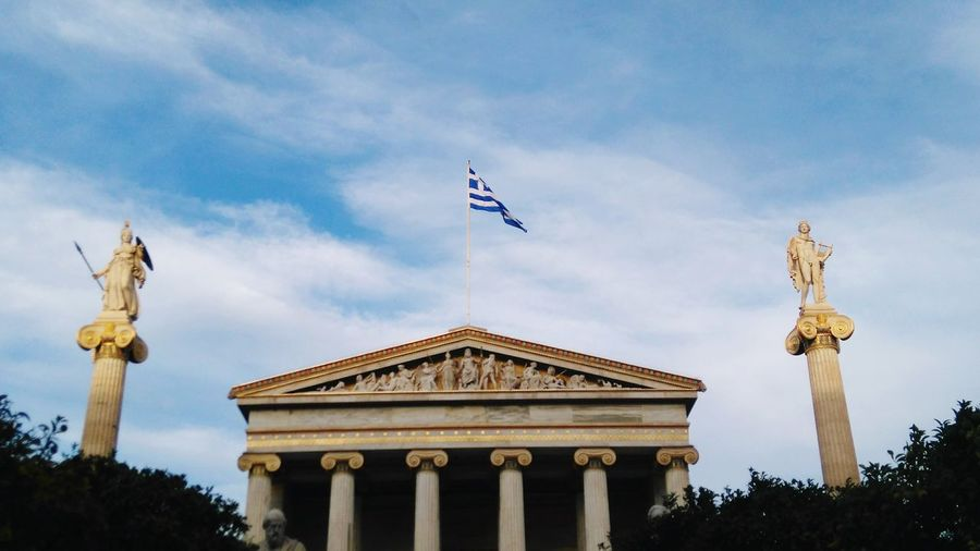 Low angle view of greek flag over academy of athens against sky