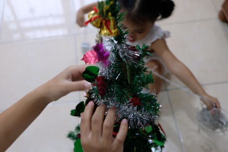 Mother and daughter decorating christmas tree at home