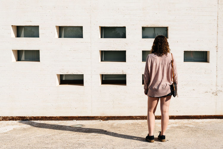 Woman standing back at modern architecture concrete building Architecture Modern Architecture Woman Abstract Architecture Building Building Exterior City Concrete Concrete Wall Day Full Length One Person Outdoors People Rear View Shadow Standing Window Young Adult