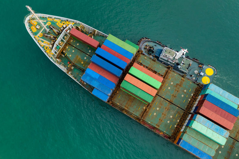 Shipping container sailing on the green sea