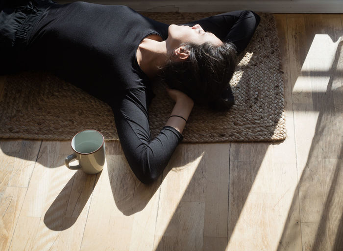 High angle view of woman lying on floor at home