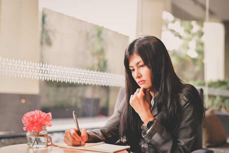 Young businesswoman writing in spiral notebook at cafe
