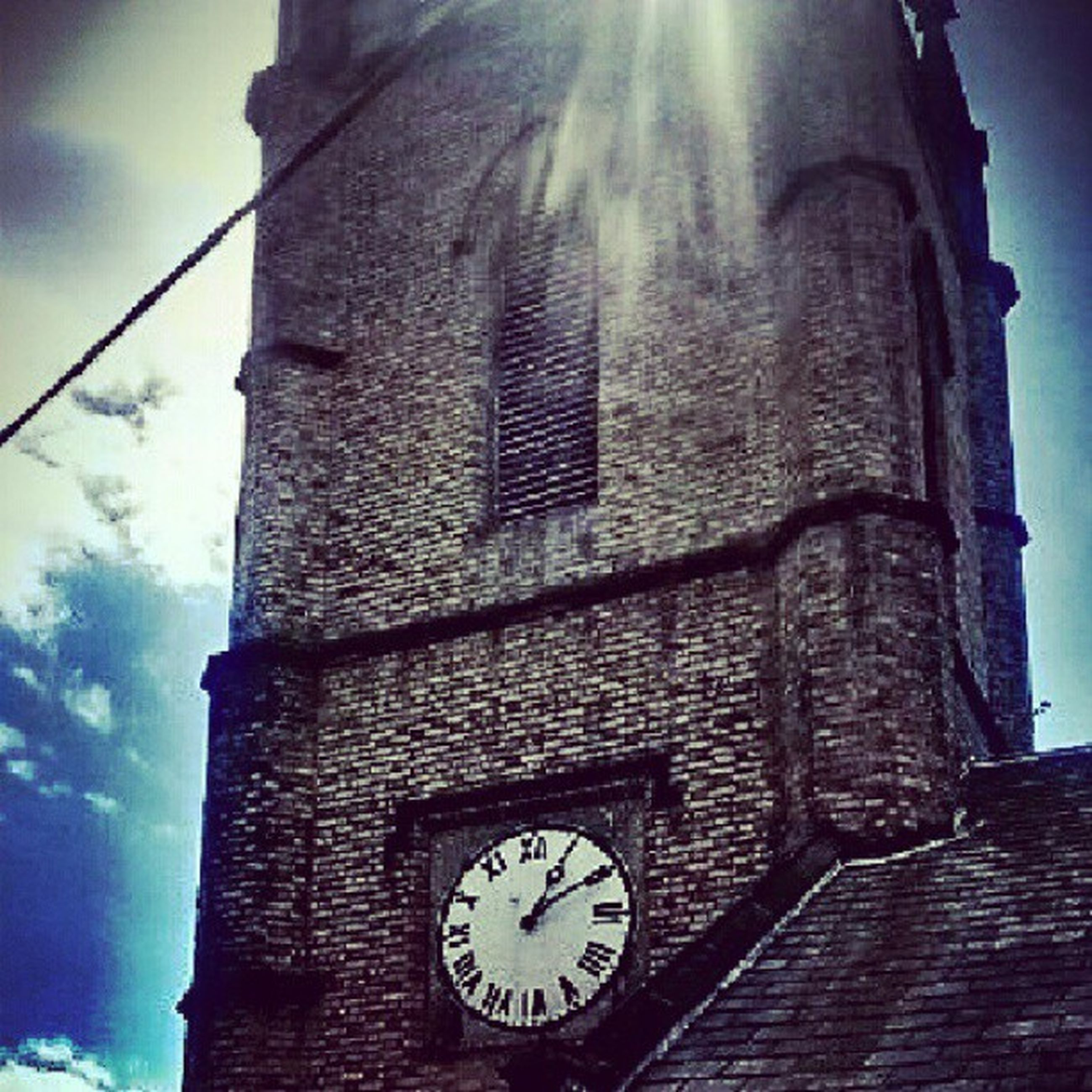 low angle view, architecture, clock, built structure, building exterior, time, clock tower, old, sky, religion, church, old-fashioned, number, history, no people, tower, cross, outdoors, wall - building feature