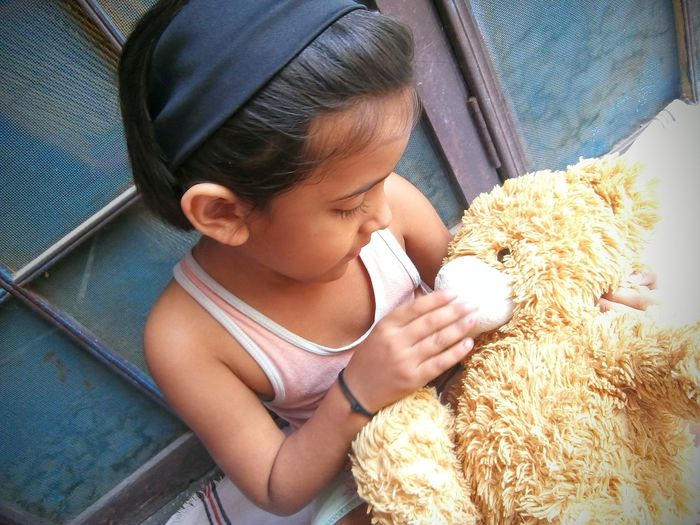High Angle View Of Cute Girl Playing With Teddy Bear While Sitting Outdoors