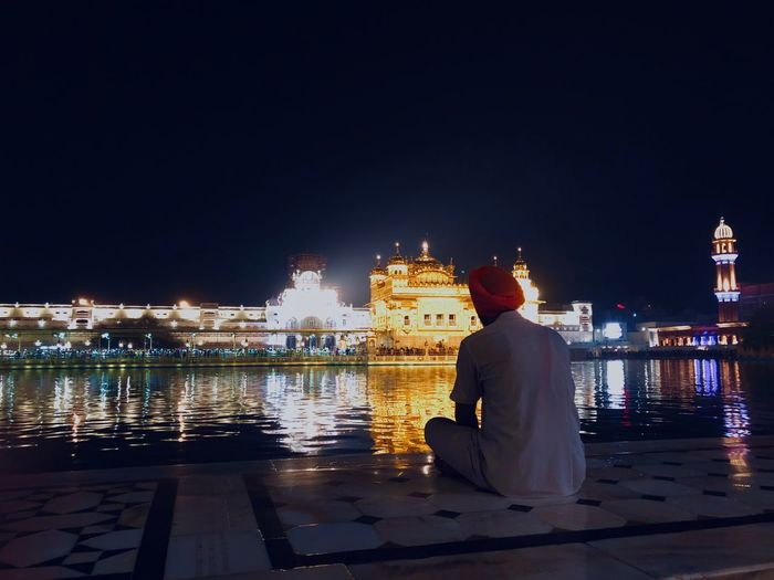 Rear view of man wearing turban sitting by river against illuminated buildings at night