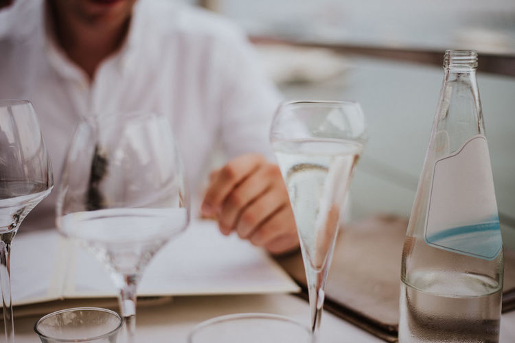 Midsection of man holding beer glass in restaurant