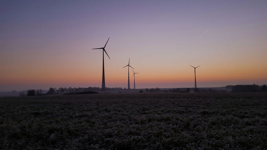 Windmills on field against clear sky at dusk
