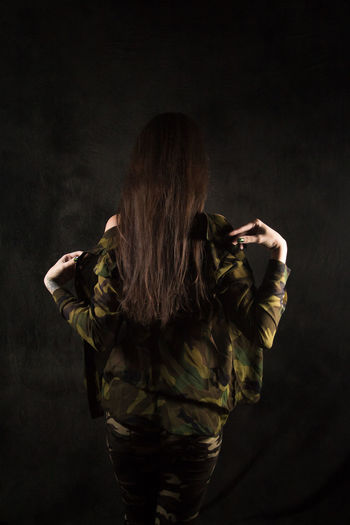 Adult Beautiful Woman Black Background Brown Hair Casual Clothing Clothing Fashion Hair Hairstyle Holding Human Hair Indoors  Long Hair Music Obscured Face One Person Rear View Standing Studio Shot Three Quarter Length Women Young Adult