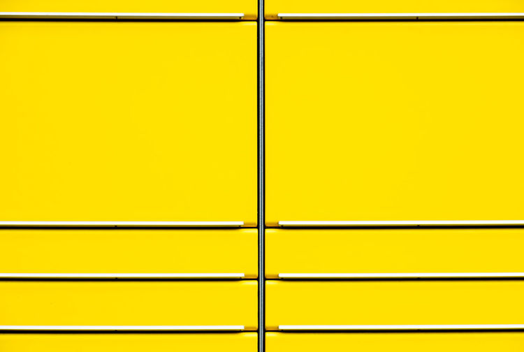 Full frame shot of yellow wall seen through metal grate