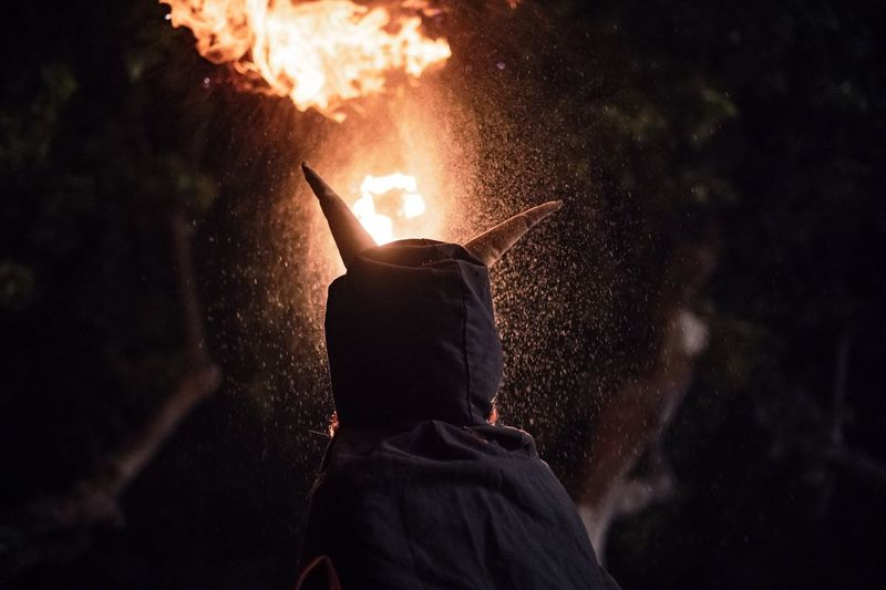 Rear view of person wearing costume while standing against fire