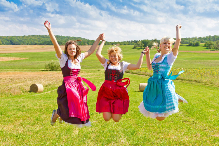 Smiling Female Friends With Dirndl Jumping Over Field Against Sky