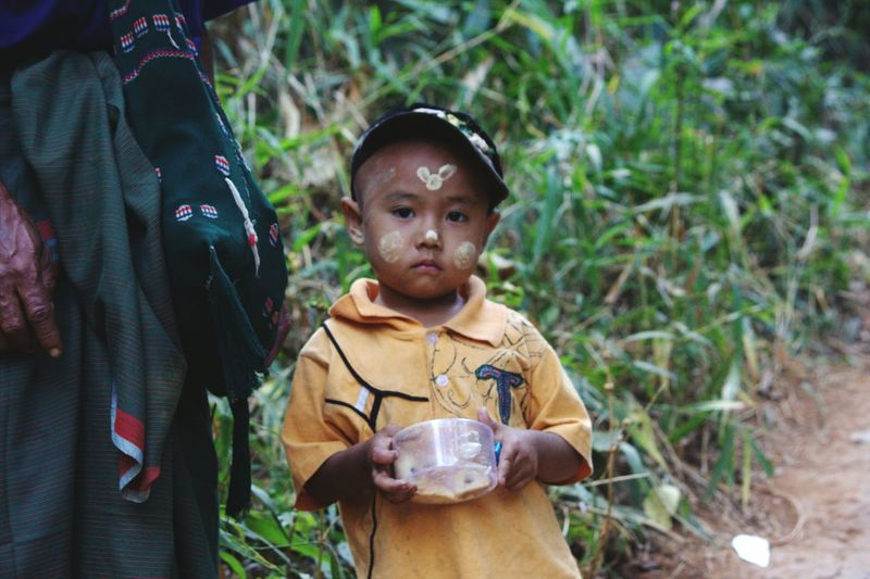 Portrait of boy with traditional face painting sanding on field