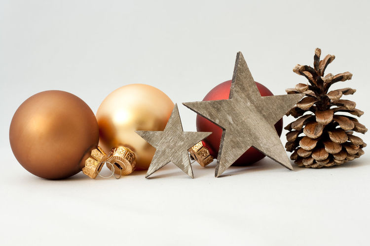 Still Life Studio Shot Indoors  White Background Close-up No People Christmas Decoration Celebration Copy Space Christmas Shape Holiday Star Shape Christmas Ornament Gold Colored Star Merry Christmas! Celebration Holidays Pine Cone Ornaments Happy Holidays! Backgrounds