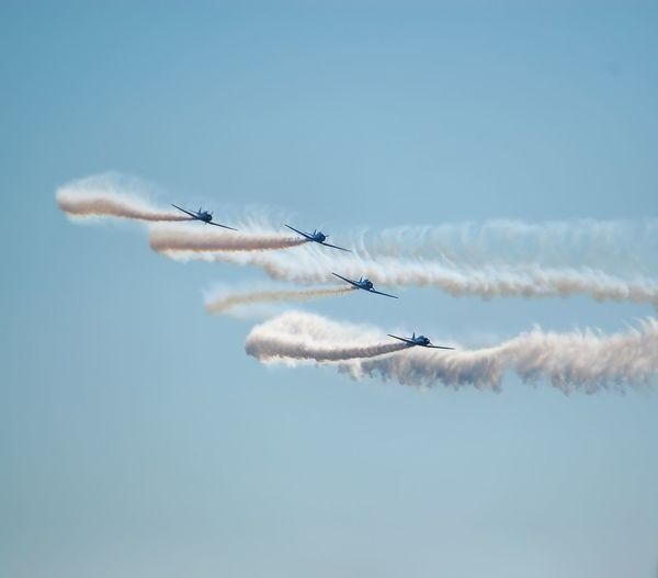 Low angle view of airshow in clear sky
