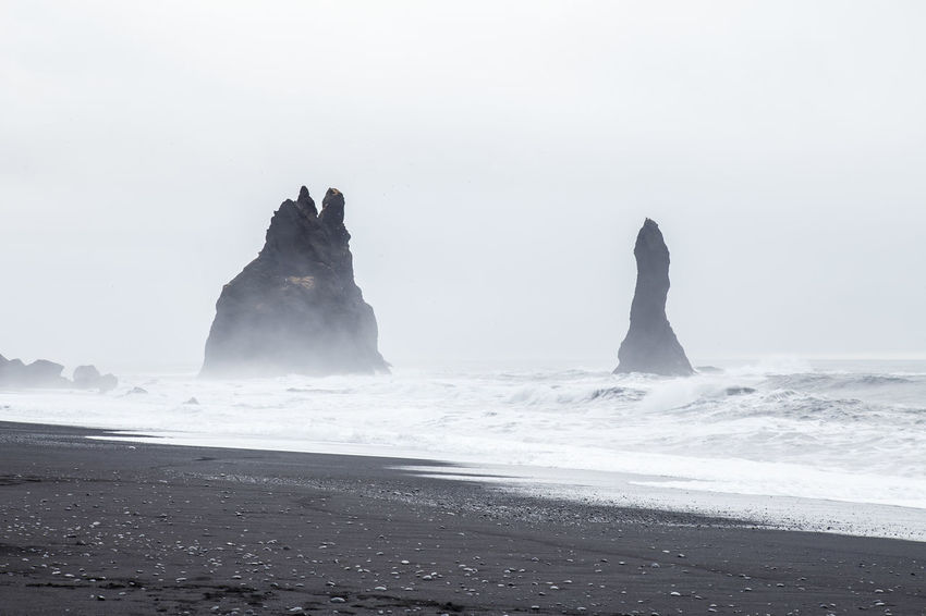 "Beautiful volcanic rock formations on black sand beach in Dyrholaey, Iceland. These formations are considered by Icelandic legends as ""trolls"" turned into stone. Atlantic Ocean Coastline Dyrhólaey Formation Iceland Nature Rock Travel Bay Black Sand Beach Destination Icelandic Landscape Ocean Outdoor Reynisdrangar Reynisdrangur Reynisfjara Sea Shore Tourism Troll Vik Volcanic  Water"
