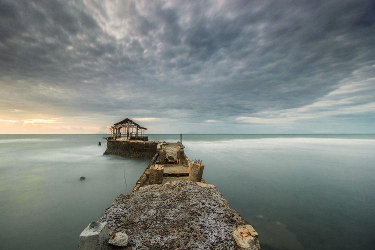 Damaged pier on sea against cloudy sky