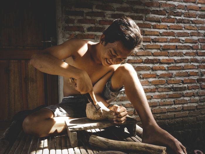 Full length of shirtless man sitting against wall while crafting kuksa