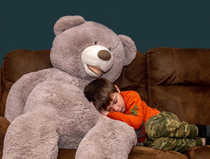 Boy sleeping on big bear
