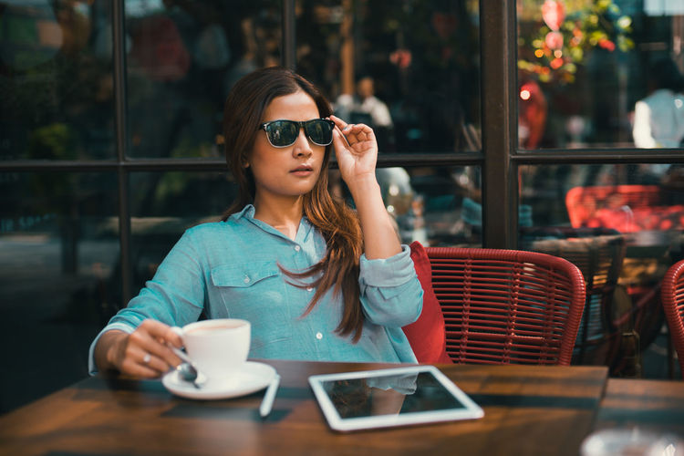 Cafe Communication Day Mobile Phone One Person Outdoors People Portable Information Device Real People Smart Phone Sunglasses Table Technology Using Phone Wireless Technology Young Adult