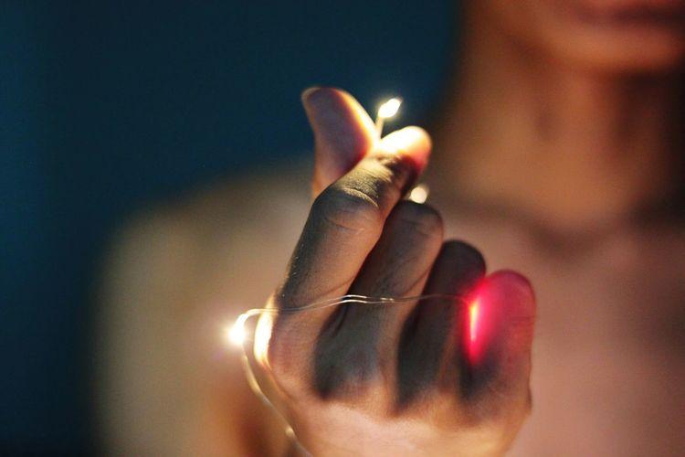 Close-up of hand holding illuminated candle