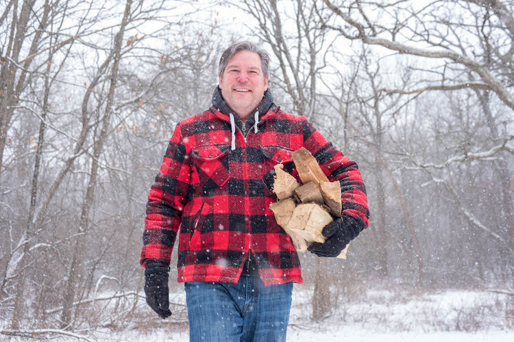 Midsection Of Mature Man With Wood During Snowfall