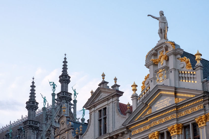 Statues on the museum rooftops in the square at La Grand-Place, Brussels. The Grand Place Tourist Attraction  Architecture Belief Building Building Exterior Built Structure Day History La Grand Place Low Angle View Museum Nature No People Outdoors Place Of Worship Religion Sculpture Sky Spire  Spirituality Statue The Past Tourist Destination Travel Destinations