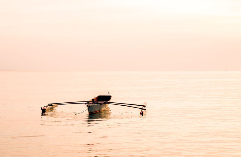Rowing boat in sea against sky during sunset