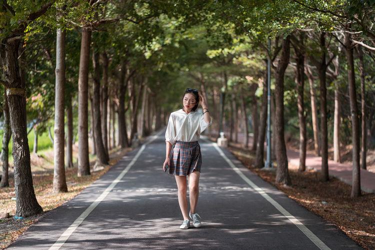 Full length of man standing on road against trees