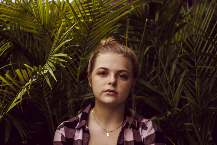 Adult Beautiful Woman Close-up Contemplation Day Focus On Foreground Front View Green Color Growth Hairstyle Headshot Leisure Activity Lifestyles Looking At Camera Nature One Person Palm Leaf Plant Portrait Real People Teenager Young Adult Young Women