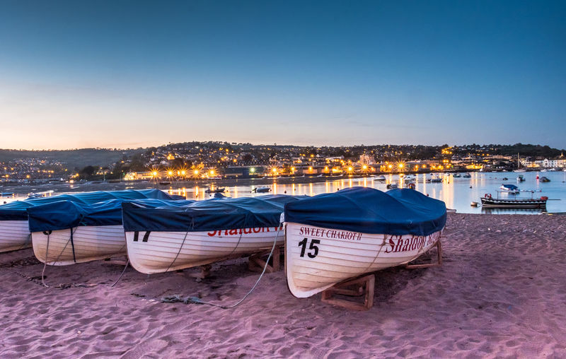 Boats moored on beach against clear sky during sunset