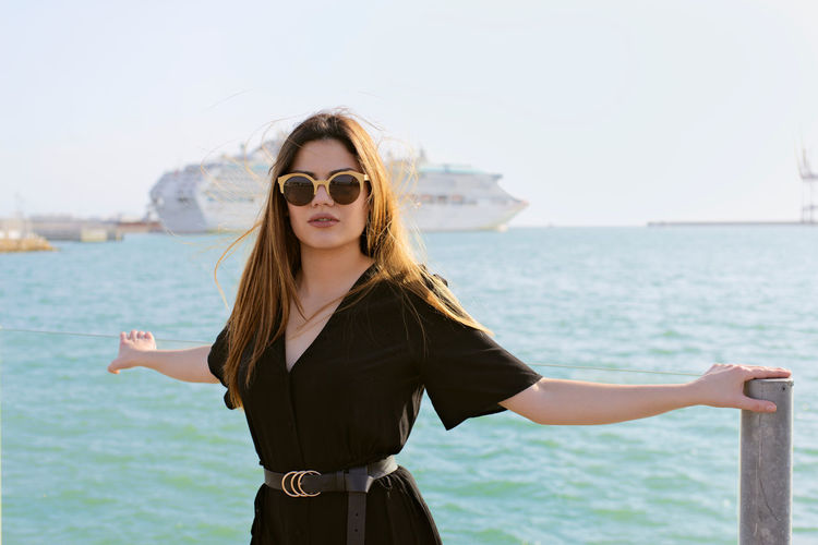 Portrait of young woman wearing sunglasses standing against sea