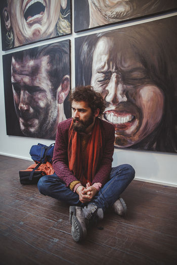 Casual Clothing Sitting One Person Real People Front View Young Adult Indoors  Lifestyles Young Men Full Length Leisure Activity Beard Facial Hair Looking Men Cross-legged Young Women Portrait Contemplation Hairstyle