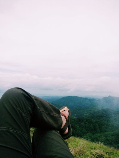 Low section of man relaxing on mountain against sky