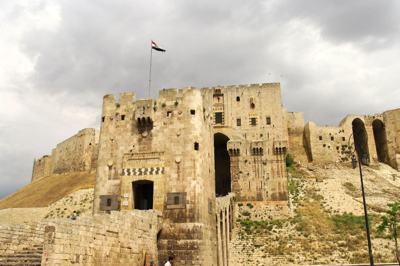 Syria  Aleppo Aleppo Castle Ancient Ancient Civilization Archaeology Architecture Bad Condition Building Exterior Built Structure Cloud - Sky Damaged Day Flag History Low Angle View Nature No People Old Ruin Outdoors Rock - Object Sky The Past Travel Destinations