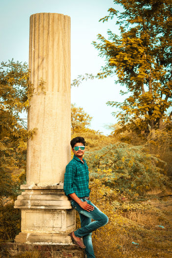 Portrait of young man standing bu column in forest