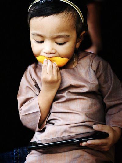 Cute girl eating mango while using smart phone