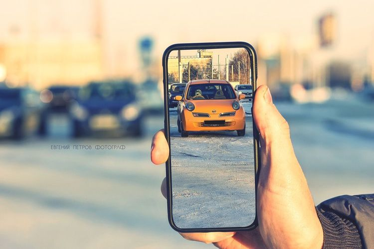 Man photographing car on street
