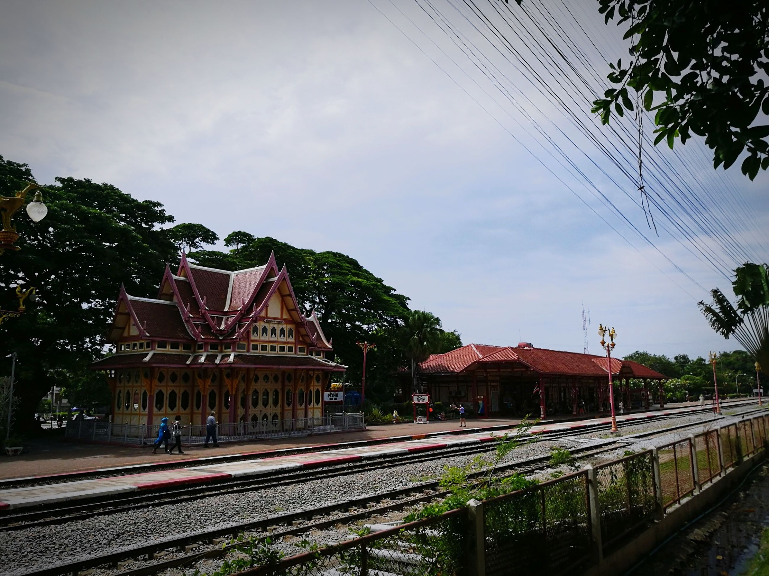 architecture, built structure, sky, building exterior, railroad track, track, rail transportation, transportation, tree, building, city, nature, cloud - sky, plant, mode of transportation, cable, no people, street, public transportation, day, electricity, outdoors