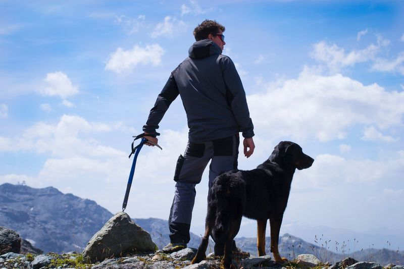 Rear view of man with dog standing against sky