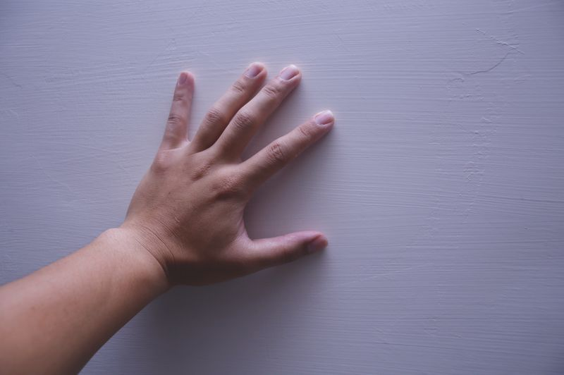 Cropped hand touching wall