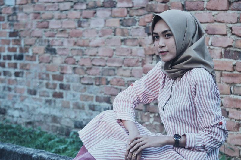 Young Woman Wearing Hijab Against Brick Wall