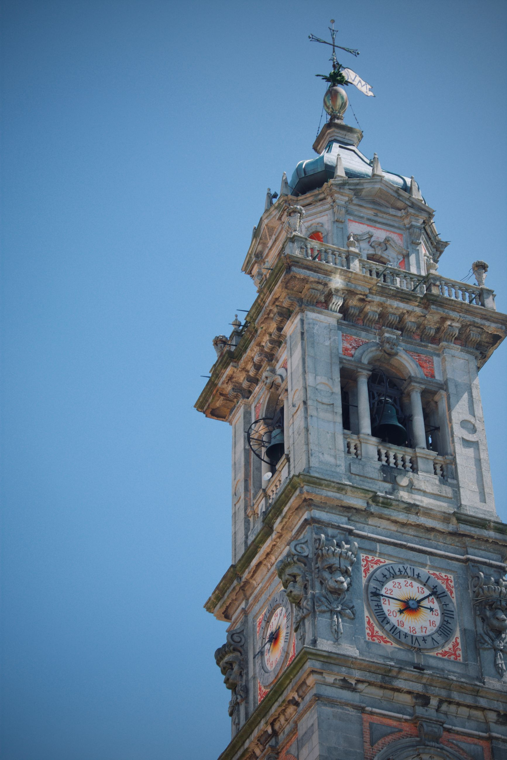 LOW ANGLE VIEW OF CLOCK TOWER BY BUILDING AGAINST SKY