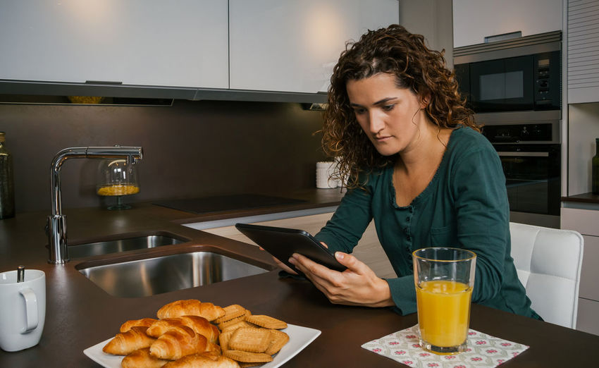 Young woman having breakfast in the kitchen and looking at the tablet Horizontal Croissant Coffee Female Girl Orange Juice  Technology Comfortable Enjoying Relax Sitting One News Modern Serious Portrait Biscuits Indoor Internet Real Curly Hair Young Concentrated Journal Sunday People Digital Holding Reading Web Napkin Shopping Looking Lifestyle Caucasian Home Kitchen Single Tranquility Morning Interested Tablet Using Breakfast Pajama Woman Unmarried