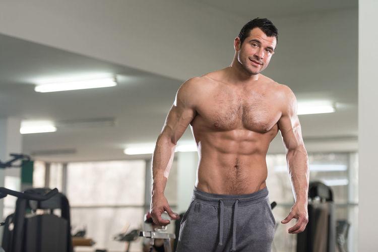 Portrait of shirtless man standing in bathroom