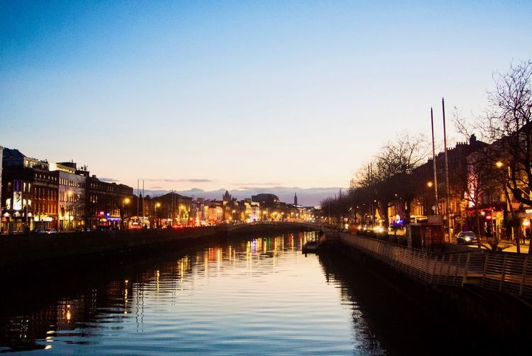 Canal by illuminated city against sky at night
